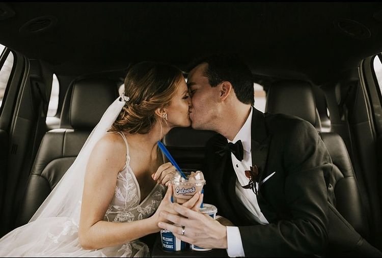 Just-married couple in car kissing and holding Culver's Fresh Frozen Custard