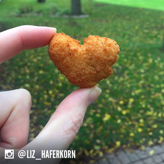 Culver's guest holding a Cheese Curd heart with green grass and trees in the background.