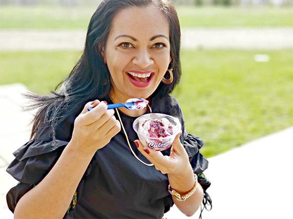 Smiling woman holds up a dish of Culver's Blackberry Cobbler Fresh Frozen Custard.