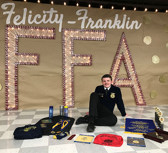 Luke poses in front of an FFA sign with a collection of FFA memorabilia.