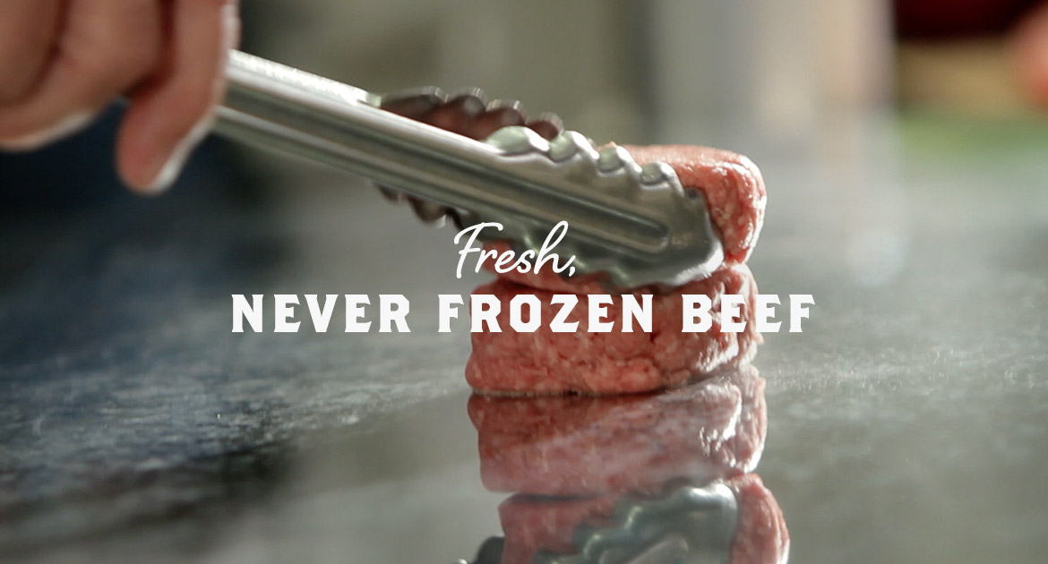 """A beef patty on the grill with """"Fresh Never Frozen Beef"""""""