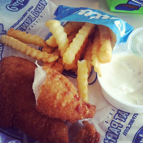 A chicken tender and crinkle cut fries from Culver's sitting on a table next to ranch dressing