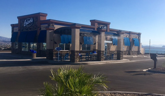 A photo of a Culver's restaurant taken from its parking lot in a desert landscape