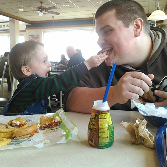 A toddler in overalls laughing while feeding a crinkle cut french fry from Culver's to a relative sitting next to him
