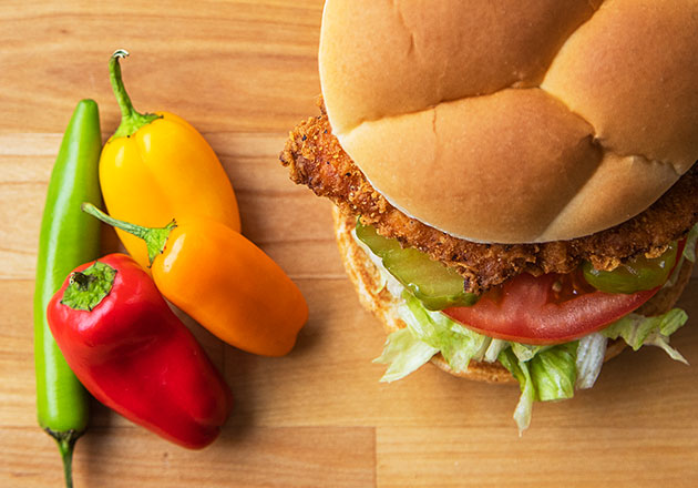 Link to story: Test Your Pepper Knowledge.The Spicy Crispy Chicken Sandwich sits next to four peppers on a wood table.