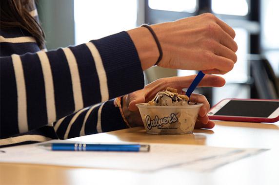 Hand begins to scoop up a bite of Culver's Fresh Frozen Custard.