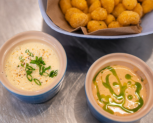 Two dipping sauces sit beside a dish of Culver's Wisconsin Cheese Curds