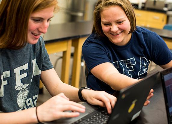 Two FFA members work on computers
