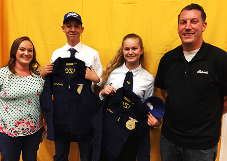 Caleb and Emily Meier present FFA blue jackets to two students.