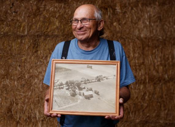 George Feltz holds an old photo of his family's farm.