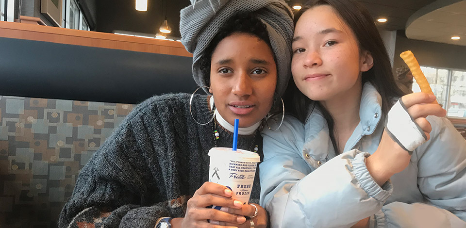 Alemitu and a friend pose with their meals in a booth at Culver's.