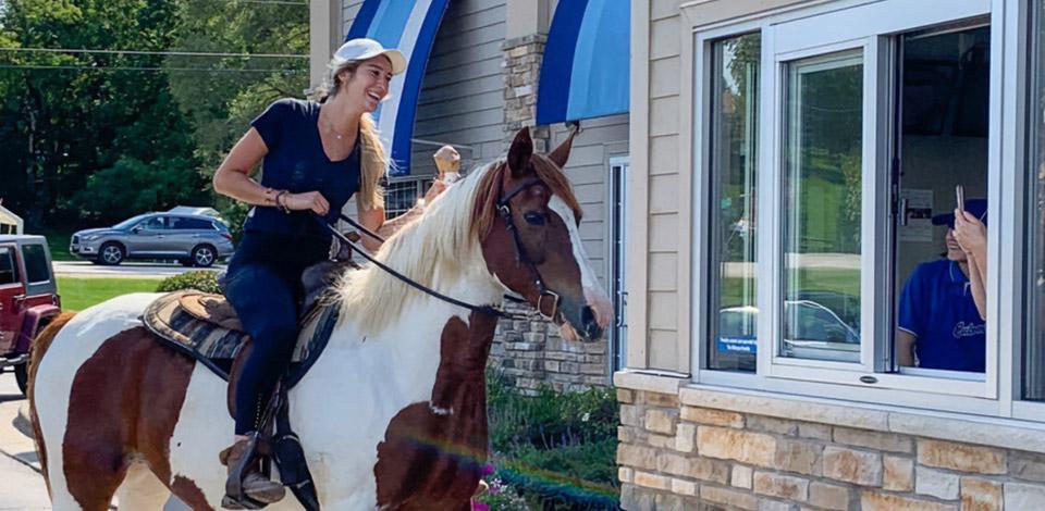 Girl riding a horse through the Culver's Drive-Thru