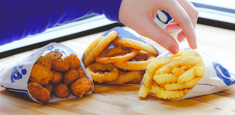 A hand reaches for Onion Rings, Crinkle Cut Fries and Cheese Curds on a table.