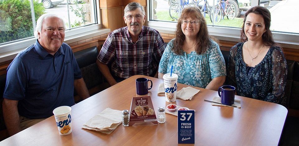 Craig Culver enjoys a meal in a corner booth with first guest Jim Olson, Jim's wife Marion and their daughter Heather.