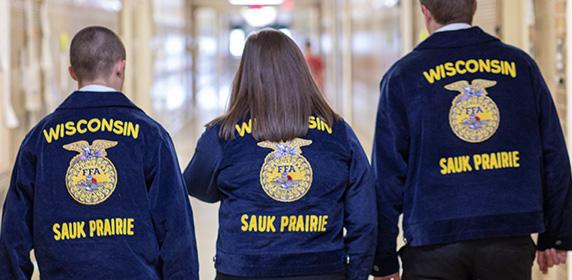 FFA students wearing FFA blue jackets, walking down a hallway