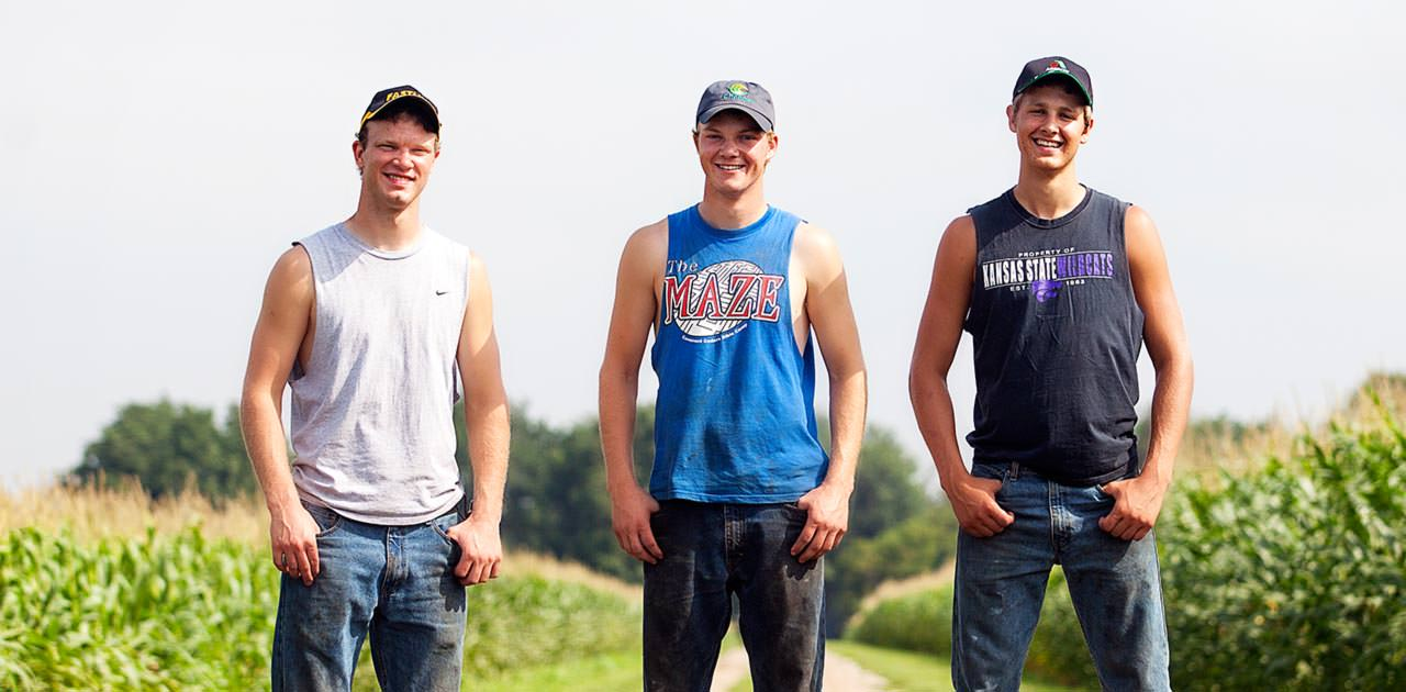 Peterson Farm Bros pose on a road between two cornfields