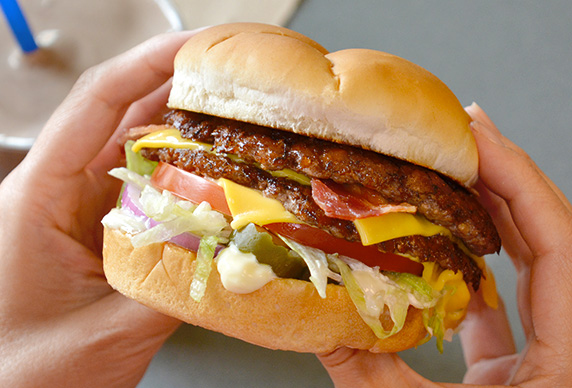 A Culver's guest with a Bacon Deluxe in their hands as they prepare to take a bite. A Chocolate Shake is in the background on the table.