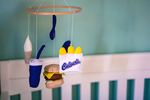A baby mobile with cheese curds, a drink cup and a ButterBurger hangs over a crib.