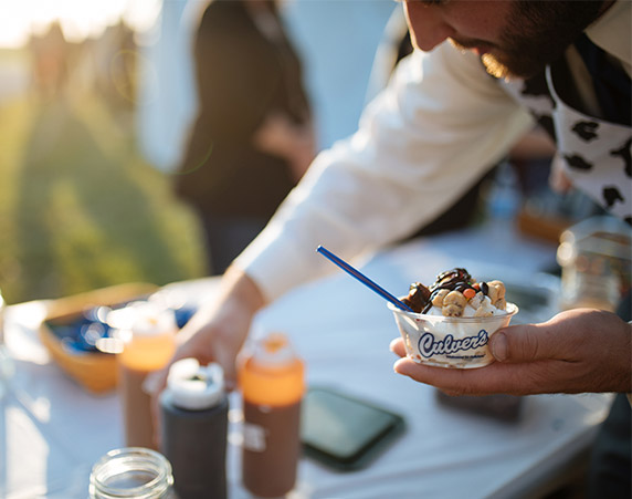 The groom, Cory, reaches for toppings to put on his dish of frozen custard.