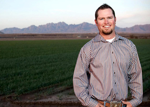Jay Hill stands in front of a green field in front of a mountain range.