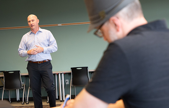 Man takes notes as Culver's CEO Joe Koss speaks.