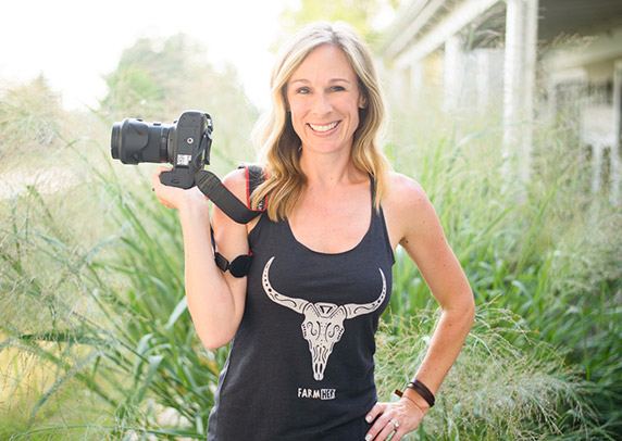 Marji Guyler-Alaniz stands in front of tall grass in a FarmHer shirt, holding her camera.