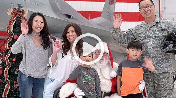 An airman with his family poses for a photo with Santa in front of an F-16 aircraft at the holiday party. Click to watch video.