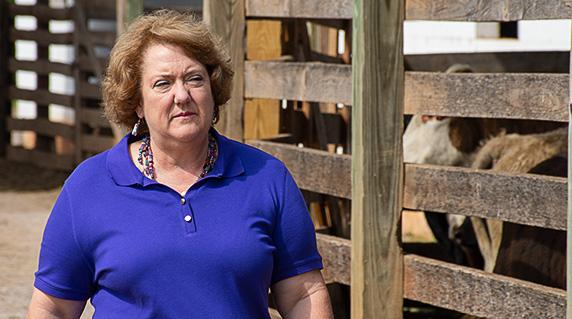 NCBA President Jennifer Houston walks near livestock barn.