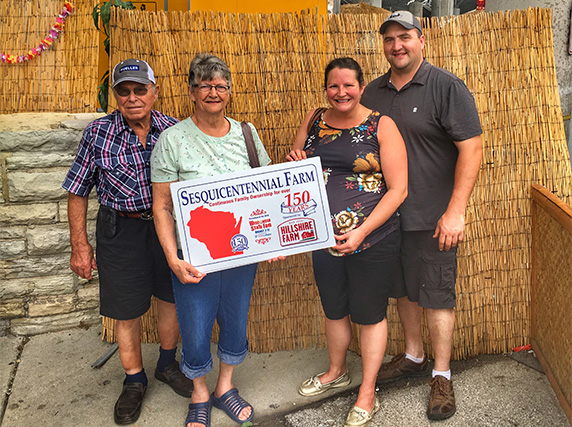 Randy, Marie and Randy's parents pose with a sesquicentennial farm sign.
