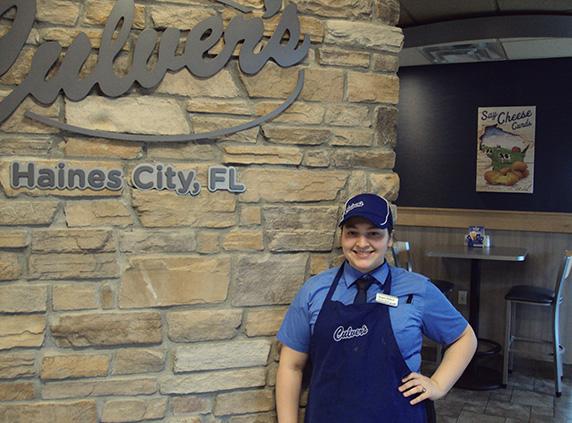 Selene stands inside the Haines City, FL restaurant wearing her True Blue Crew uniform.