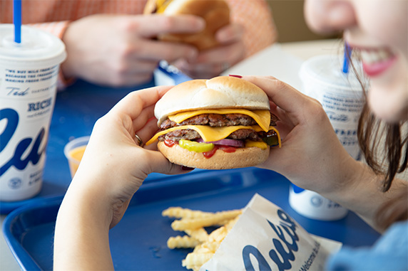 Woman holds Culver's ButterBurger Cheese in both hands.