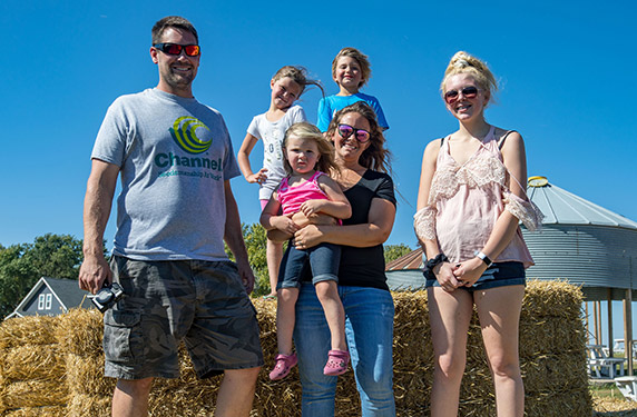 Zach and his family posing for a photo on their farm.