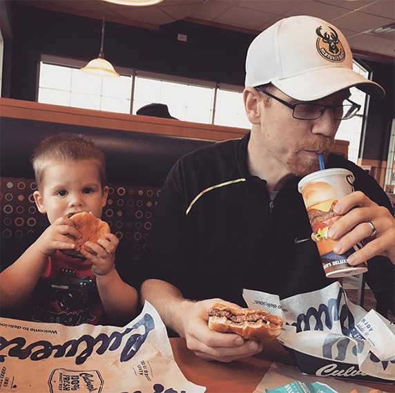 Young boy eating Culver's ButterBurger® next to father who has a ButterBurger® in his hand and is sipping his drink