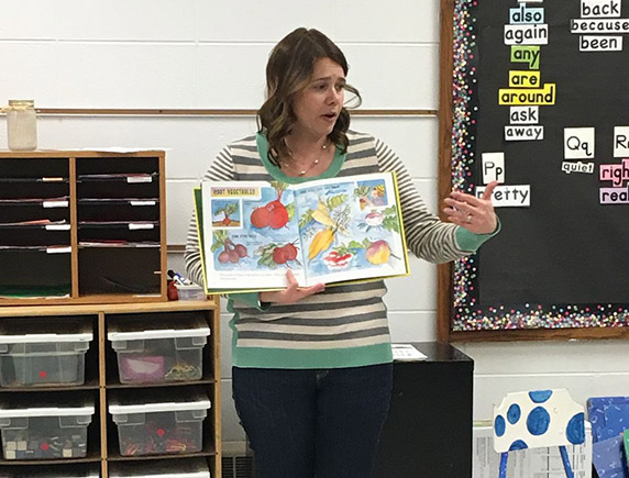 Katie Pratt hold a book in front of a classroom.