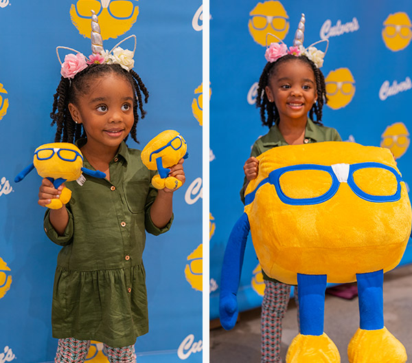 A young girl holds up Curdis plushes and smiles for a photo in front of a Culver's backdrop
