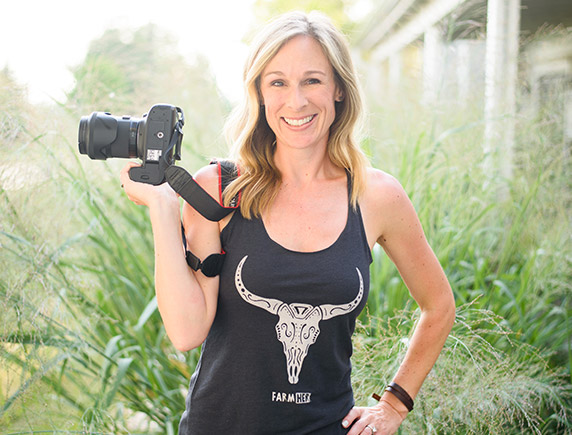 Marji Alaniz stands in a yard with tall grass while holding a camera.