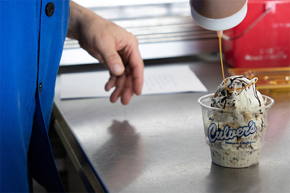 A dish of Culver's Fresh Frozen Custard is drizzled with caramel.