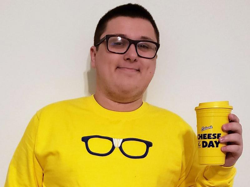 Kurtis Culver wearing a yellow Curd Nerd sweatshirt and holding a Curd Nerd travel cup