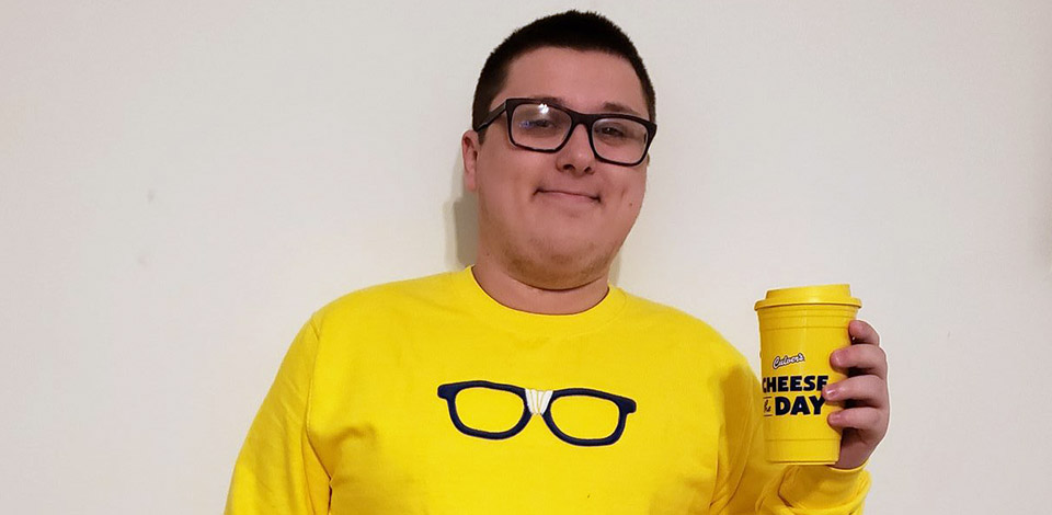 """Kurtis Culver wearing a yellow Curd Nerd sweatshirt with black framed glasses, and holding a """"Cheese the Day"""" yellow travel mug"""