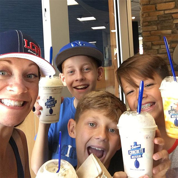A mom and three young sons hold up their Vanilla Concrete Mixers in a Culver's restaurant.