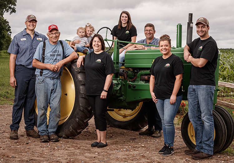 Link to story: Do you know where your food comes from? A group shot of the Feltz family, children, parents and grandparents gathered together posing in front of their green tractor.