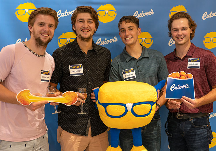 A group of young men take a photo with cheese curd props in front of a Culver's backdrop