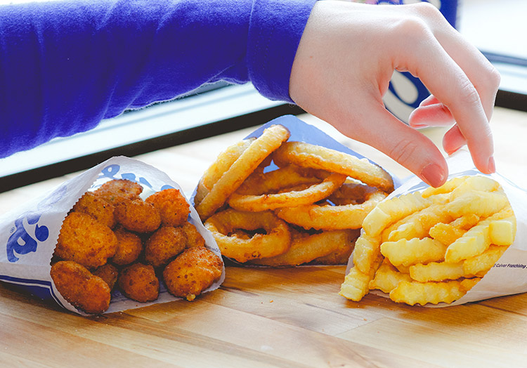Link to story: Can we guess which side you're craving? A hand reaches for Onion Rings, Crinkle Cut Fries and Cheese Curds on a table.