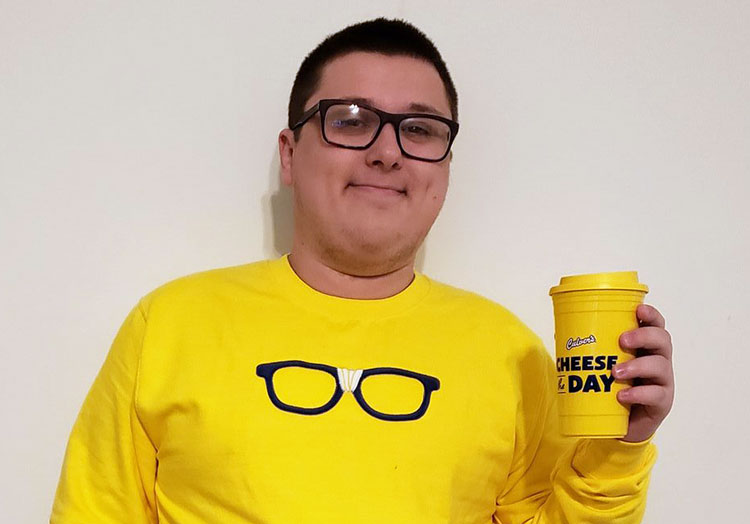 """Link to story: Culver's Guest has same name as restaurant. Kurtis Culver wearing a yellow Curd Nerd sweatshirt with black framed glasses, and holding a """"Cheese the Day"""" yellow travel mug."""